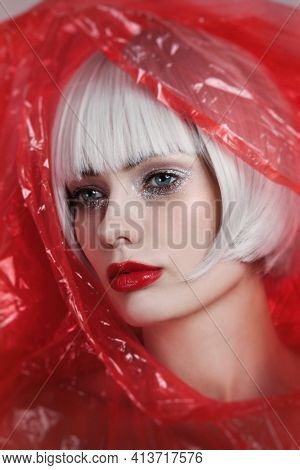 Vintage style portrait of young beautiful woman with platinum blonde hair wearing red plastic raincoat