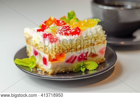 A Portion Of Cream Cake With Pieces Of Colorful Jelly And Sprinkled With Coconut Flakes