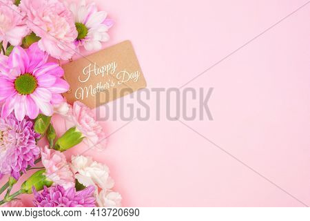 Happy Mothers Day Gift Tag With Side Border Of Pink And White Flowers. Top View On A Pink Background
