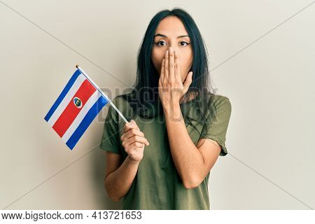 Young hispanic girl holding costa rica flag covering mouth with hand, shocked and afraid for mistake. surprised expression