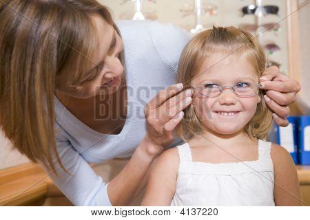 Vrouw probeert bril op jong meisje op Optometristen glimlachen