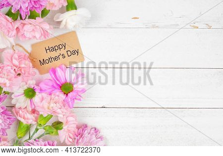 Happy Mothers Day Gift Tag With Side Border Of Pink And White Flowers. Overhead View On A White Wood
