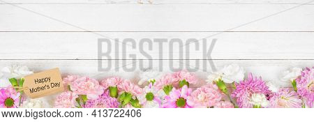 Happy Mothers Day Gift Tag With Long Bottom Border Of Pink And White Flowers. Top View On A White Wo