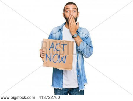 Attractive man with long hair and beard holding act now banner covering mouth with hand, shocked and afraid for mistake. surprised expression