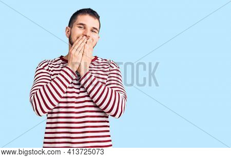 Young handsome man wearing striped sweater laughing and embarrassed giggle covering mouth with hands, gossip and scandal concept