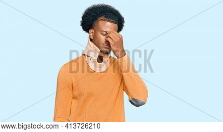 African american man with afro hair wearing cervical neck collar tired rubbing nose and eyes feeling fatigue and headache. stress and frustration concept.