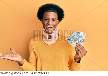 African american man with afro hair wearing cervical neck collar and holding money from insurance celebrating achievement with happy smile and winner expression with raised hand