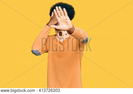 African american man with afro hair wearing cervical neck collar covering eyes with hands and doing stop gesture with sad and fear expression. embarrassed and negative concept.