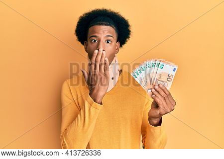 African american man with afro hair wearing cervical neck collar and holding money from insurance covering mouth with hand, shocked and afraid for mistake. surprised expression