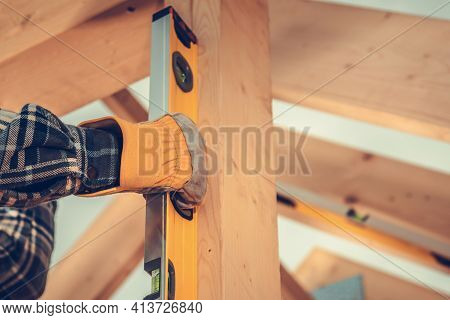 Industrial Theme. Construction Contractor Checking Home Frame Levels Using Sprit Level Tool. Close U