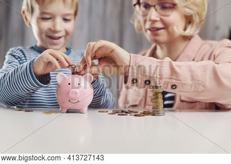 Three Years Old Child And Young Woman Sitting At The Table With Money And Piggybank. Happy Boy With