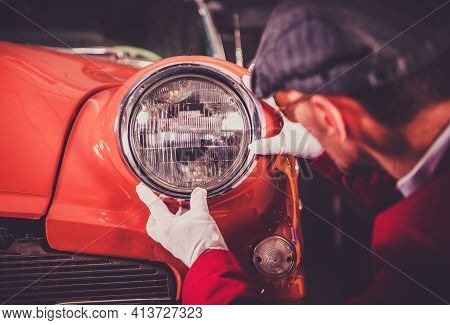 Caucasian Hobbyist In White Gloves Restoring Dark Orange Reddish Body Vintage Car. Front Headlamp Ch