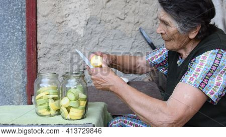 Wrinkled Senior Asian Woman Slices Raw Yellow Squash For Homemade Canning With Dill Seeds And Garlic