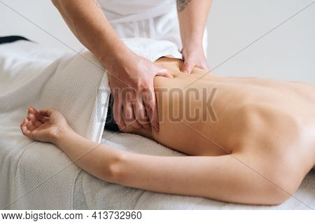 Side View Of Male Masseur Massaging Lower Back Of Young Woman Lying On Massage Table On White Backgr