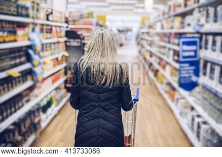Back View Of Woman Shopping In The Supermarket. Consumerism Lifestyle.