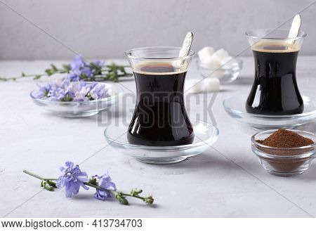 Chicory Beverage In Two Glass Cups, With Concentrate And Flowers On Light Gray Background. Healthy H