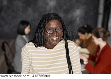 Waist Up Portrait Of Young African-american Woman Smiling At Camera In Office With Diverse Group Of