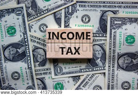 Income Tax Symbol. Concept Words 'income Tax' On Wooden Blocks On A Beautiful Background From Dollar