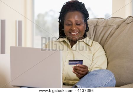 Woman In Living Room Using Laptop Holding Credit Card And Smiling