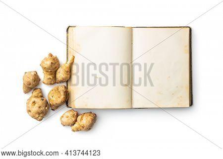 Blank cookbook and raw jerusalem artichoke. Topinambur vegetable root isolated on white background.