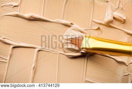 Foundation, concealer, face make-up smudge, smear. Cosmetic liquid foundation or cream beige color smudge, smear, stroke. Contouring, Makeup smears background. Brush. Foundation texture.
