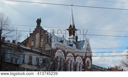 One Of The Buildings In Odessa Against A Cloudy Sky With A Spire And A Cross.