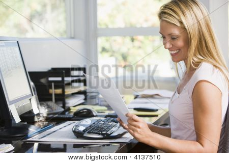 Woman In Home Office With Computer And Paperwork Smiling