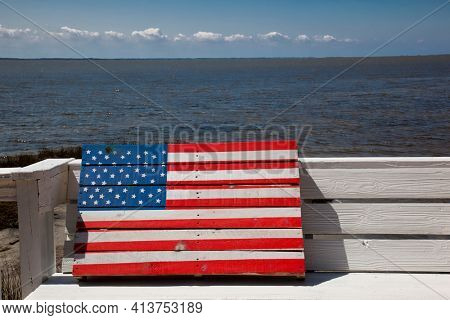 A wooden American flag sits on a bench along the water in the town of Duck in the Outer Banks of North Carolina. This is a popular vacation destination for travel.