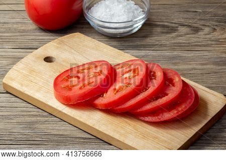 Tomato Sliced Into Round Slices On A Wooden Cutting Board