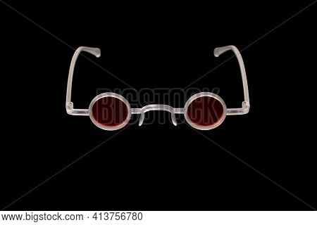 Red Round Glasses In White Frame On Black Background. Creative And Fashionable Glasses.