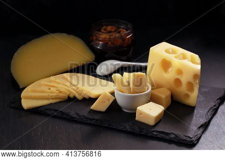 Several Types Of Cheese In Chunks, Cut Into Slices And Pieces In White Bowl With Jar Of Nuts On Blac