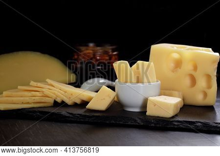 Several Types Of Cheese In Chunks, Cut Into Slices And Pieces In Bowl With Spoon And Jar Of Nuts On