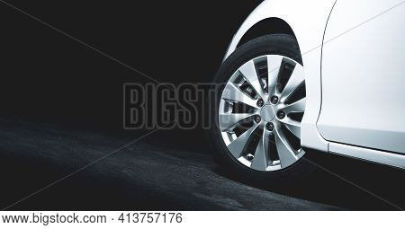Alloy Wheels Of The White Car Are Turning On The Cement Road Of Parking Lot With Copy Space On The L