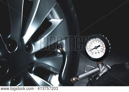 Mechanic Testing The Tire Pressure With Tire Pressure Gauge