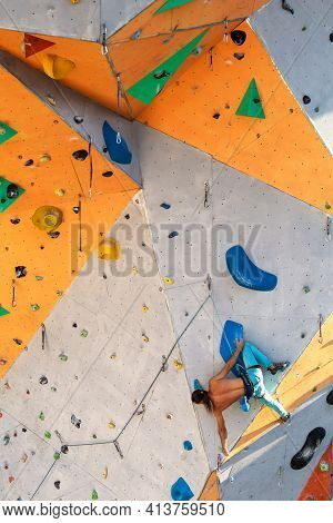 A Man Climbs A Climbing Wall, A Climber Is Training On Artificial Terrain, Rock Climbing In The City