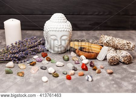 Selection Of Precious And Semiprecious Stones. Ceramic Statuette Of A Buddha Head. White Pillar Cand