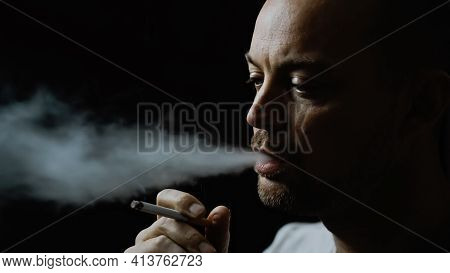 Man Smoking A Cigarette And Blowing Smoke Out Of His Mouth. Isolated On Black Background With Shallo