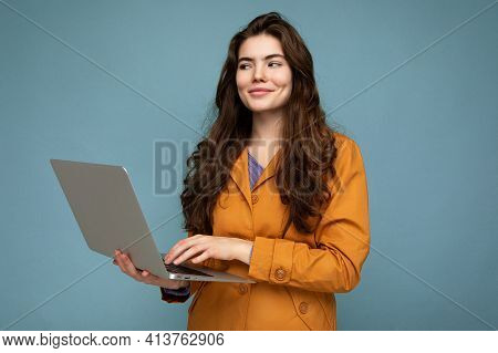 Beautiful Brunet Curly Young Woman Holding Netbook Computer Looking To The Side Wearing Yellow Jacke