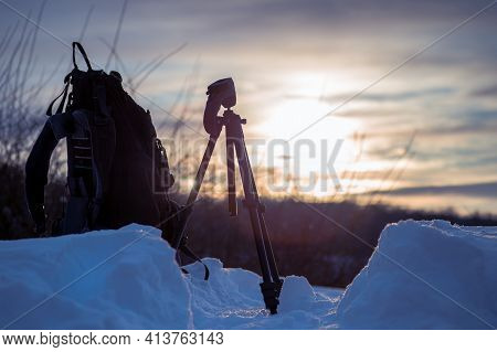 A Photographers Backpack And Tripod On The Snow At Sunrise On A Winter Morning. Traveling And Relax