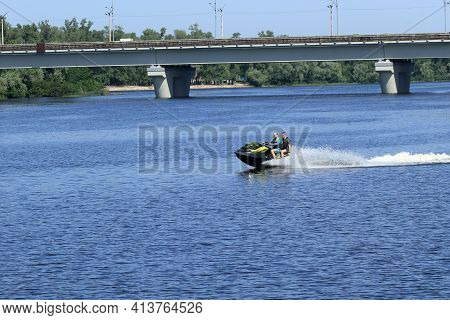 Kyiv Ukraine, The Dnieper River - June 12 2020:. Two Adult Men Ride A Jet Ski On A Wide River. Water