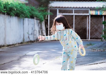 Cute Asian Girl Playing Throw A Ring. Child Wear Mask In Public Areas. Prevent The Spread Of Coronav