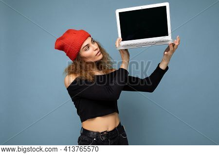 Close-up Portrait Of Beautiful Self-confident Dark Blond Curly Young Woman Holding Laptop Computer L