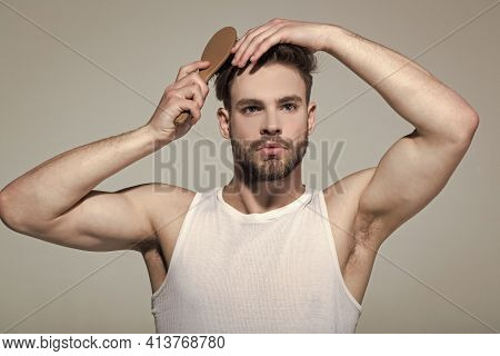 Man Brush Hair With Hairbrush On Grey Background. Guy Morning Hygiene, Haircare, Hairstyle Concept