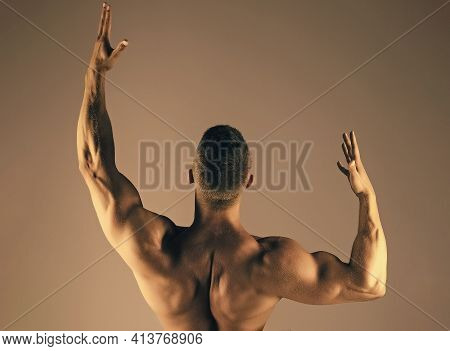 Man Bodybuilder With Muscular Back Raise Hands Biceps, Triceps. Sport, Fitness, Health Concept.