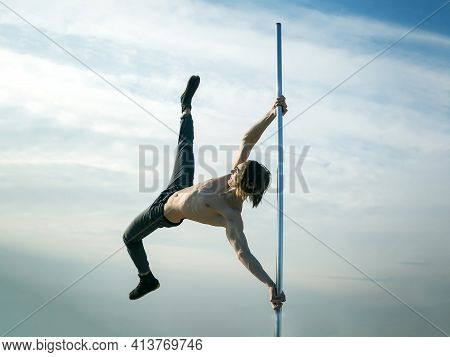 Young Strong Man Pole Dancing. Pole Dance Sport. Pole Dance Training Of Young Man Dancer On Blue Sky