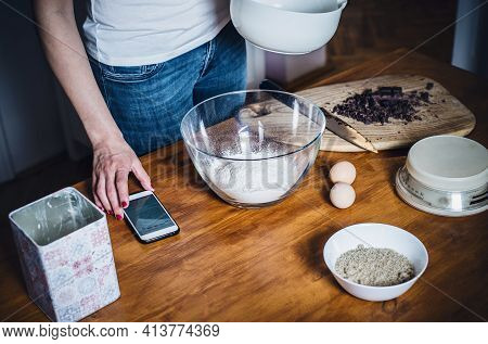 Woman cooking food in kitchen. Young woman cooking food in kitchen using tablet computer to learn. Domestic lifestyle. Cooking food. Beautiful woman cooking food at home. Lifestyles. Food. Healthy food. Modern woman food lifestyle.