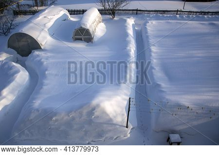 Snow Covered Vegetable Garden In The Countryside. The Greenhouses Are Completely Covered In Snow. Su