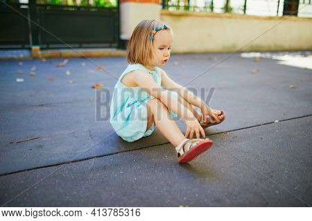 Unhappy And Emotional Toddler Girl Sitting On The Floor Outdoors. Misbehaving Child On The Street. T