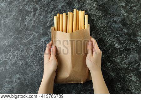 Female Hands Hold Paper Bag With Grissini Breadsticks On Black Smoky Background