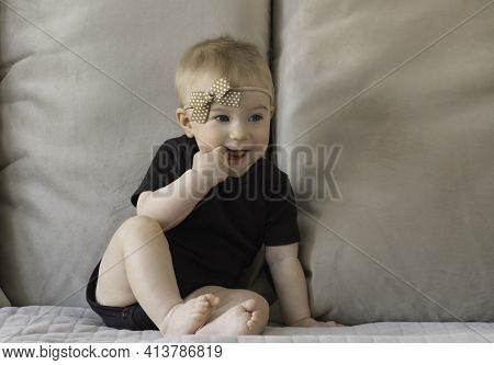 Cute Funny Caucasian Blonde Baby Girl, Sitting On Background Of Beige Sofa Pillows In Black Body Wit